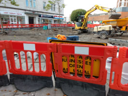 A sign saying businesses open as usual obscured by a roadworks barrier.